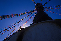 Tibetans tying new prayerflags on Buddhist Boudha Stupa for the new year.