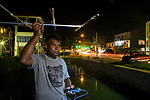 Fishing Cat (Prionailurus viverrinus) biologist, Maduranga Ranaweera, tracking cat next to canal in city at night, Urban Fishing Cat Project, Diyasaru Park, Colombo, Sri Lanka