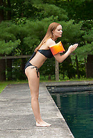 Woman wearing water wings, diving into pool