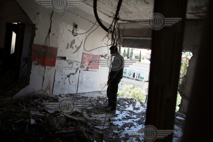 A Syrian soldier stands in the room of an apartment block that was hit by unknown projectiles.