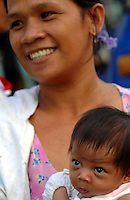 A mother and newborn in slum area of Manila called San Anreas Bukid (neighbour-hood) where families commonly have between 6- 12 children. There is no family planning available from the Government due to a law passed by the Mayor and they are too poor to pay for their own contraception.