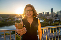 Selfie portrait taken on a smartphone of a beautiful young brunette with glasses and long hair in casual dress posing on a balcony Lady Bird Lake and the Austin Skyline during sunset.