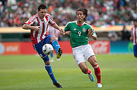 Antolin Alcaraz (5) kicks the ball ahead of Aldo De Nigris (9). Mexico defeated Paraguay 3-1 at the Oakland Coliseum in Oakland, California on March 26th, 2011.