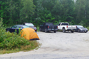 Tent setup in the Randolph East parking lot along Pinkham B Road (Dolly Copp Road) in Randolph, New Hampshire on August 16, 2020 at 7:03 AM. Overnight camping at trailhead parking lots in the White Mountains is not allowed. License plates of the vehicles in the parking lot have been blurred out.