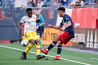 FOXBOROUGH, MA - MAY 16: Brandon Bye #15 of New England Revolution passes the ball forward under pressure from Derrick Etienne Jr. #22 Columbus SC during a game between Columbus SC and New England Revolution at Gillette Stadium on May 16, 2021 in Foxborough, Massachusetts.