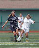 Seacoast United Phantoms player Carly Gould (3) and Boston Aztec midfielder Riley Houle (22) battle for the ball. In a Women's Premier Soccer League (WPSL) match, Boston Aztec (white) defeated Seacoast United Phantoms (blue), 3-0, at North Reading High School Stadium on Arthur J. Kenney Athletic Field on on June 25, 2013.