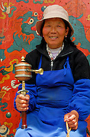 Tibetan Buddhist woman meditates with prayer wheel and rosary beads in front of image of snow lion, sacred iconic symbol of Tibet, in the Barkhor area of Lhasa, Tibet.