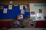 Runcorn Town 1 Runcorn Linnets 0, 26/12/2013. The Pavilions, North West Counties League Premier Division. Two elderly male supporters reading their programmes in the tea room inside the ground before the Boxing Day derby match between Runcorn Town and visitors Runcorn Linnets at the Pavilions, Runcorn, in a top-of the table North West Counties League premier division match. Runcorn Linnets won 1-0 and overtook their neighbours at the top of the league in a game watched by 803 spectators. Runcorn Linnets were a successor club to Runcorn FC, one of England foremost non-League clubs of the 1970s and 1980s. Photo by Colin McPherson.