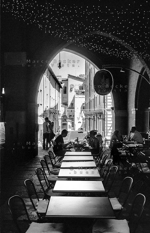 Bologna, una coppia pranza seduta ai tavolini di un ristorante sotto i portici --- Bologna, a couple sitting and having lunch at the tables of a restaurant under the portici