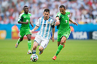Lionel Messi of Argentina takes on Peter Odemwingie of Nigeria