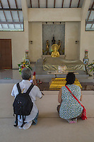 Borobudur, Java, Indonesia.  Mendut Buddhist Monastery. Visitors in the Prayer Room for Visitors to Offer Homage to the Buddha.  The man is taking a photo.