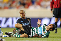 Helder Postiga (23) of Sporting Clube de Portugal goes down in pain off a tackle by Vincent Kompany (33) of Manchester City F. C. Sporting Clube de Portugal defeated Manchester City F. C. 2-0 during a Barclays New York Challenge match at Red Bull Arena in Harrison, NJ, on July 23, 2010.