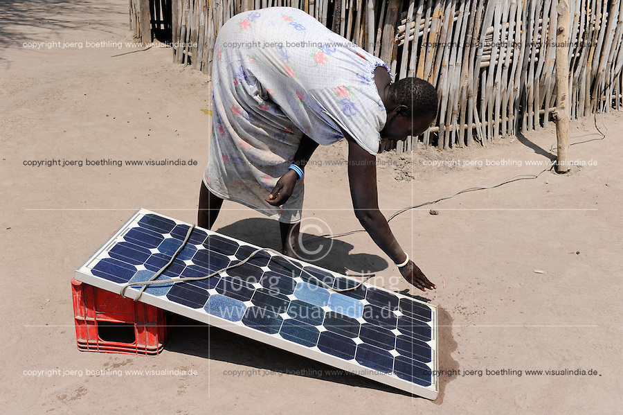 SOUTH SUDAN, Rumbek, woman clean Photovoltaic panel / SUED SUDAN Rumbek , Frau reinigt Solar Home System