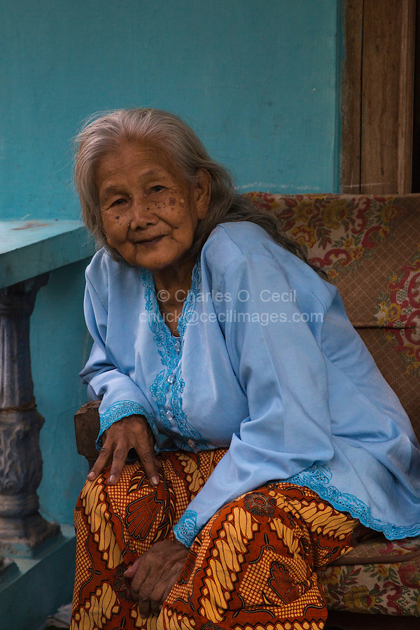 Borobudur, Java, Indonesia.  Elderly Javanese Woman Sitting on her Front Porch.