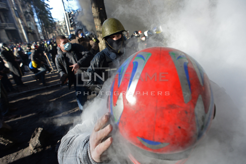 A protester wearing a helmet escapes tear gas during the clashes in Maidan square. Kiev, Ukraine