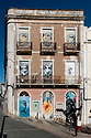 Street art decorating the boarded up windows of a three storey building, Sesimbra, Portugal.