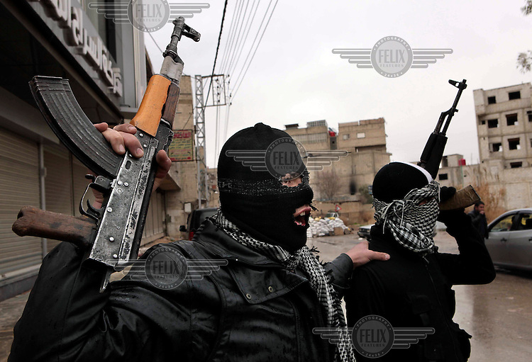 Disguised members of the Free Syrian Army, an armed group that has risen up against the regime of President Bashar al-Assad, raise their weapons defiently while patrolling in the Sakba district of Damascus. The Free Syrian Army claims to be predominately made up of deserters from the regular army who objected to being called on to shoot protesting civilians.