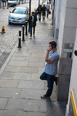 A young man speaks on a mobile phone on a street in Southwark, London.