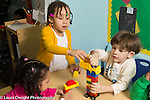 Education Preschool 3 year olds two girls and a boy playing with construction made from connecting plastic bricks (duplo)