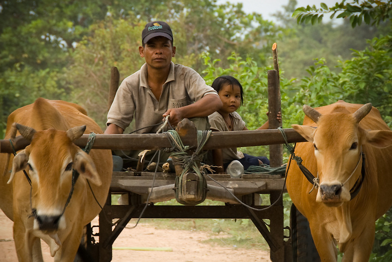 A man and daughter ride in his carriage in a rural village outside of Siem Reap. The average family in Cambodia lives on less than a dollar US per day -- and even lower in rural areas such as this one.