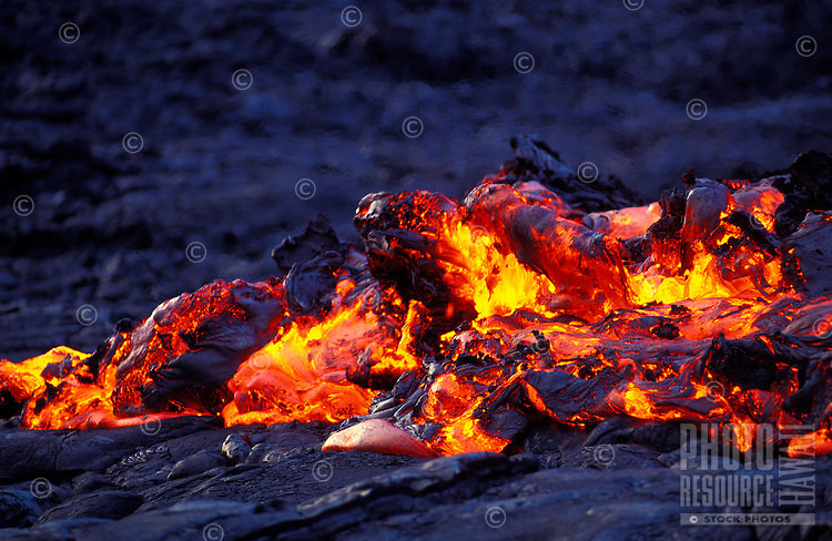 """Lava known as """"a'a lava"""" creates a glowing mass over black hardened lava."""