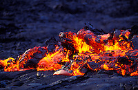 "Lava known as ""a'a lava"" creates a glowing mass over black hardened lava."