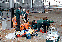 Emergency service personnel attend an incident where a construction worker fell from working on scaffolding and as a serious head injury, a cervical collar placed on him and whilst one paramedic performs CPR another is bagging him.  This image may only be used to portray the subject in a positive manner..©shoutpictures.com..john@shoutpictures.com