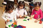 Education Preschool 3 year olds three girls playing separately at table with blocks or magnetic plastic construction toy