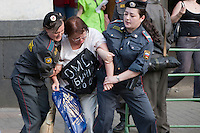 "Moscow, Russia, 31/05/2010..OMON riot police arrest a demonstrator wearing a banner saying ""The OMON murdered my son"" as they break up an opposition protest in central Moscow and arrest around 170 people. Opposition activists hold regular demonstrations on the 31st day of the month, protesting against restrictions on the freedom of assembly, which is protected by article number 31 of the Russian constitution."