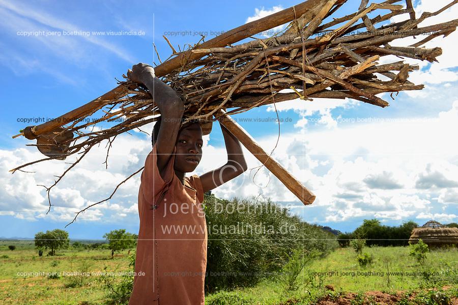 UGANDA, Karamoja, Kaabong, Karamojong boy carry firewood on the head / Karamojong Ethnie, Dorf Lochom, Junge traegt Feuerholz