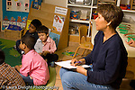 Preschool New York City ages 4-5 female teacher talking notes as class participates in circle time horizontal