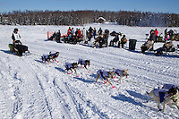 Sunday, March 4, 2012  Nicolas Petit runs on Long Lake past spectators on a picnic at the restart of Iditarod 2012 in Willow, Alaska.