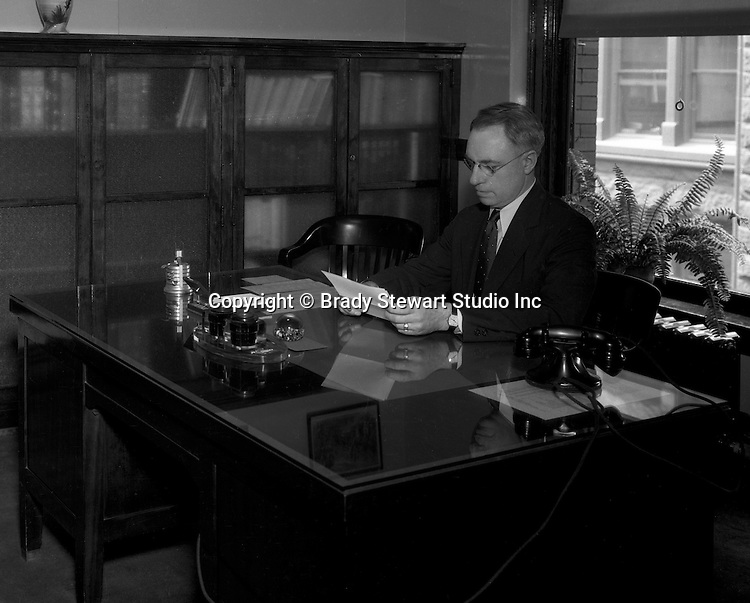 Pittsburgh PA: Administrator reading documents in his office at Duquesne University.