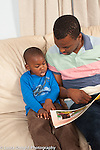 Father reading picture book to 3 year old son