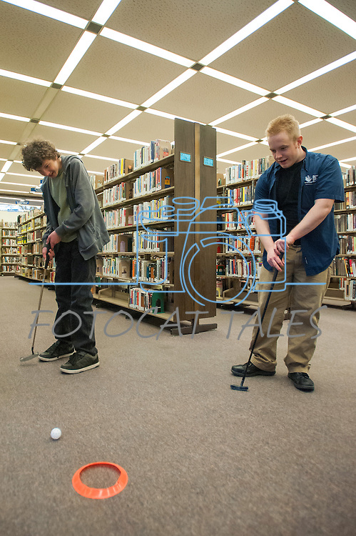 Ryan Fitzsimmons attempts a putt while Carson City Library Assistant Aubrey White watches during the Mini Golf Night at the Carson City Library on Friday May 9, 2014. Kids and parents built a custom mini golf course throughout the library using anything at their disposal and engineering ideas to make a difficult course. Everything from tables to shelves were used to create creative courses.<br /> (Photo by Kevin Clifford/Nevada Photo Source)