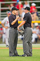 Umpires Jimmy Lott (left) and Drew Freed discuss a play during the Appalachian League game between the Danville Braves and the Burlington Royals at Burlington Athletic Park on July 18, 2012 in Burlington, North Carolina.  The Royals defeated the Braves 4-3 in 11 innings.  (Brian Westerholt/Four Seam Images)