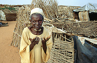 Sudan. West Darfur. Ryiadh. Ryiadh is located on the outskirts of the town of Al Geneina and is a camp for internally displaced people (IDP)) from the civil war. An elderly man, begs for hepl near his  poor living wood hut. © 2004 Didier Ruef