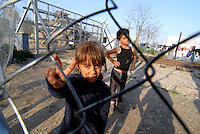 Idomeni / Greece 04042016<br /> Children living along the railway lines in Idomeni refugge camp.<br /> On the background the fance dividing Greece to Fyrom and one Makedonia Army armored vehicle.<br /> Photo Livio Senigalliesi