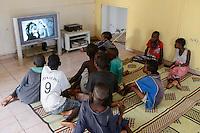 DJIBOUTI Caritas project for street children, children watch DVD via TV / DSCHIBUTI katholische Kirche, Caritas Projekt fuer Strassenkinder, Kinder schauen DVD Koenig der Loewen auf dem Fernseher im Gemeinschaftsraum