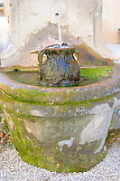 A fountain and urn with running water and moss at Chateau Saint Cosme, Gigondas, Vaucluse, Rhone, Provence, France