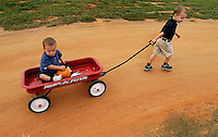 A young boy pulls his brother in a red Flyer wagon during a visit  to a pumpkin patch in North Carolina.