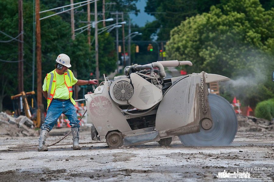A worker guides a concrete saw across the Main Street Bridge spanning Alum Creek to cut the bridge surface intosmall section as demolition work begins on the structure