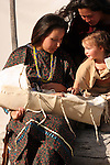 A young Native American Indian women with her baby in a cradle and another mom and her baby girl visiting