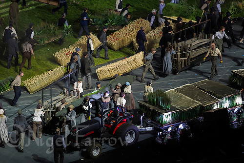 """27 JUL 2012 - LONDON, GBR - Actors playing farmworkers remove the rural scenery and props at the start of the """"Pandemonium"""" section of the Opening Ceremony of the London 2012 Olympic Games in the Olympic Stadium in the Olympic Park, Stratford, London, Great Britain (PHOTO (C) 2012 NIGEL FARROW)"""