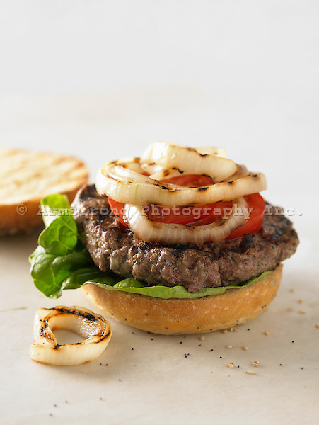 Gourmet hamburger with lettuce, tomato and grilled onion. On kaiser roll, pictured open-faced.