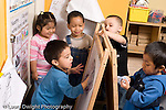Educaton preschool  3-4 year olds group of children playing together around dry erase easel horizontal