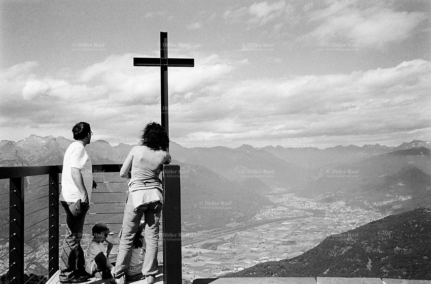 Switzerland. Canton Ticino. Monte Tamaro. A couple with their children stands by the chapel Santa Maria degli Angeli which offers an unique viewing terrace and a large panorama on the swiss Alps. The chapel was build by the swiss well-known architect Mario Botta. Monte Tamaro is a mountain reaching a height of 1,962 meters. 25.06.06 © 2006 Didier Ruef