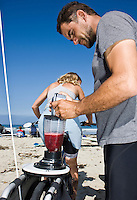 """Saturday, June 21 2009.  Pacific Beach, San Diego, CA, USA:  Dr. Marcus and his wife Eriksen and Anna Cummins of the environmental group Algalita Marine Research Foundation (AMRF) make breakfast with a bicycle-powered blender in PB one day after completing a six-week journey from Vancouver to TJ to raise awareness about marine debris.   The couple spoke at 40 different events along the way and presented 5 mayors with samples of the """"plastic soup"""" that they collected form a remote part of the Pacific Ocean known as the North Pacific Gyre.  The confluence of currents in that area of the Pacific has created a high concentration of marine debris - particularly plastics - that is clogging the area, endangering marine life and entering our food chain."""