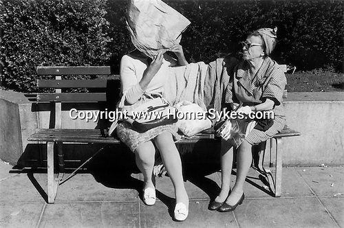 Two older women chatting in a  downtown park, one has made a bonnet  from a brown paper bag to shield her self from the sun. San Francisco, California. 1971. 1970s USA