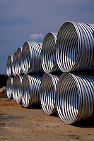 Large aluminum drainage pipes are stacked up at a construction site.